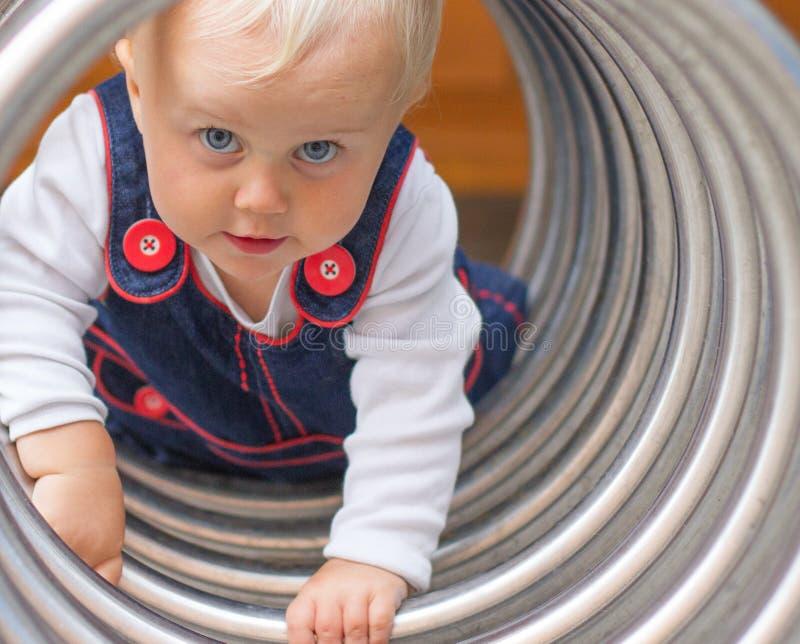 Bambina sveglia che striscia tramite il tunnel immagine stock libera da diritti