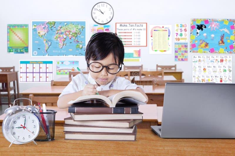 Bambina sveglia che studia nell'aula fotografia stock