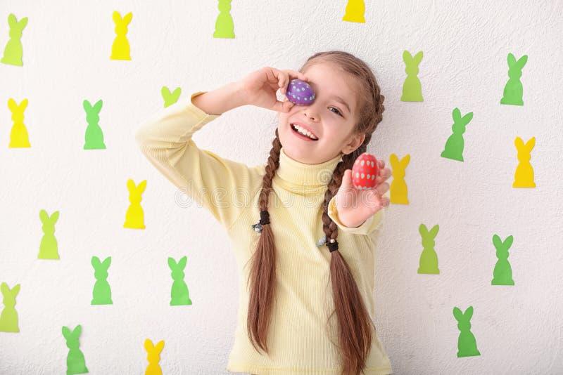 Bambina sveglia che tiene le uova di Pasqua vicino alla parete bianca decorata con i coniglietti di carta fotografia stock