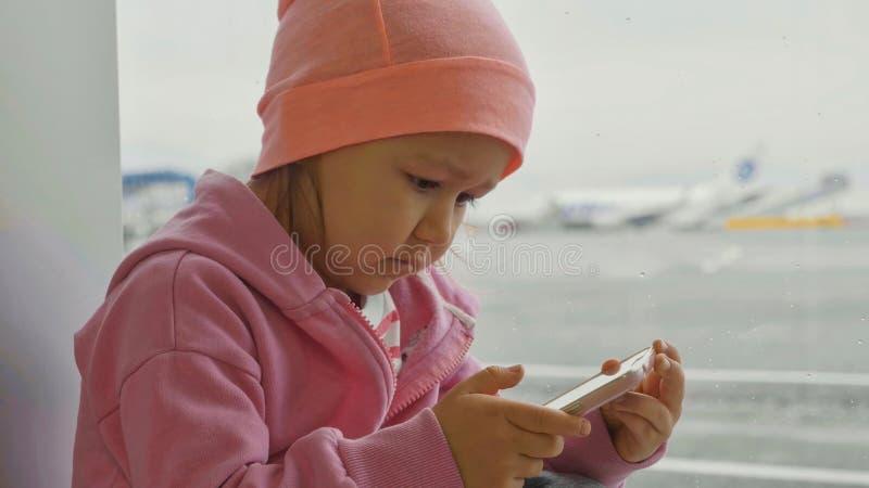 Bambina sveglia che utilizza Smart Phone nell'aeroporto, primo piano immagini stock libere da diritti