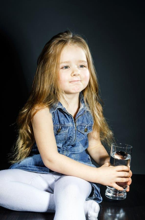 Bambina sveglia con capelli lunghi che tengono bicchiere d'acqua immagine stock libera da diritti