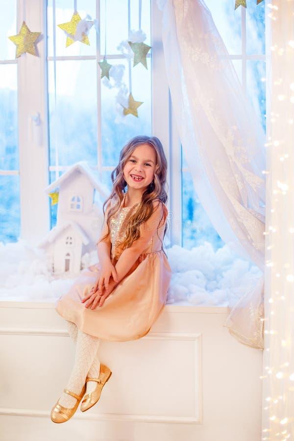 Bambina sveglia con capelli ricci alla finestra in attesa di magia del nuovo anno e di Natale immagine stock