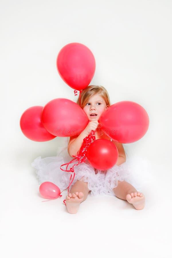 Bambina sveglia con gli aerostati rossi fotografie stock libere da diritti