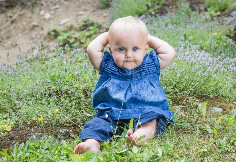 Bambina sveglia con i bei occhi azzurri che si siedono nel giardino fra i fiori fotografia stock