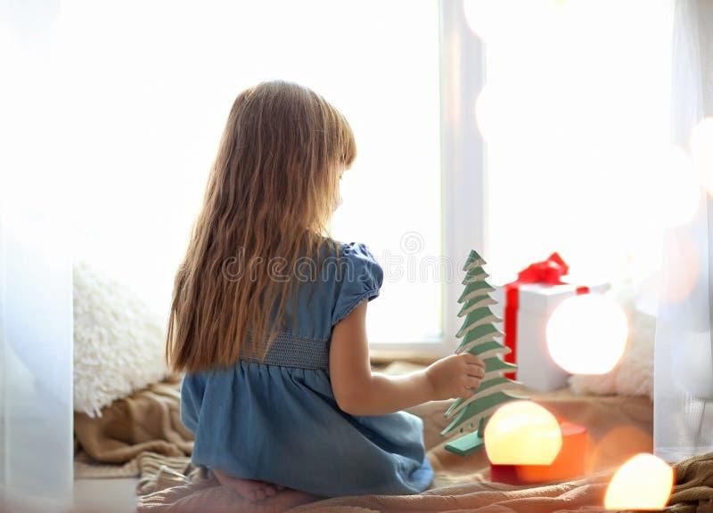 Bambina sveglia con i contenitori di regalo che si siedono davanzale vicino posteriore a casa immagine stock