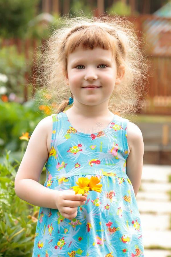 Bambina sveglia con i fiori fotografie stock