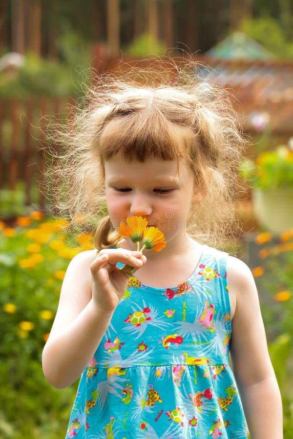 Bambina sveglia con i fiori immagine stock