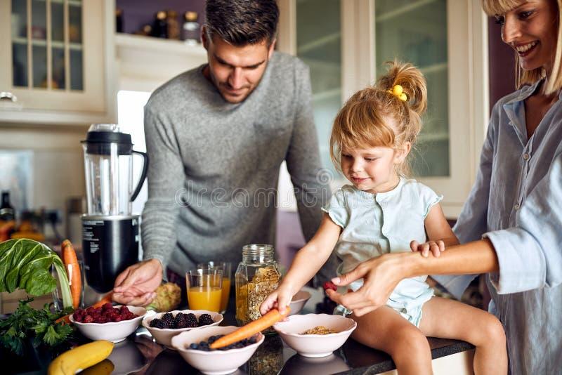 Bambina sveglia con i genitori che preparano prima colazione fotografia stock