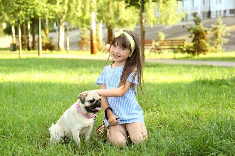 Bambina sveglia con il cane del carlino in parco il giorno di estate fotografia stock libera da diritti