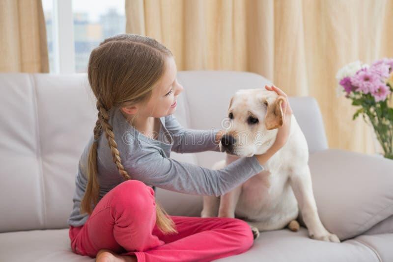 Bambina sveglia con il suo cucciolo sullo strato fotografia stock libera da diritti