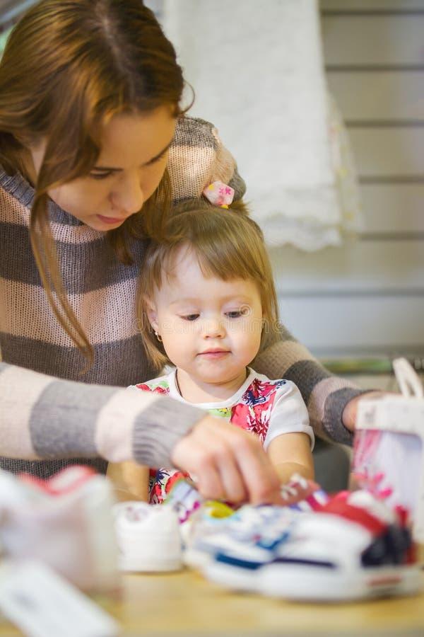 Bambina sveglia con la sua mamma che sceglie le scarpe al negozio di vestiti immagine stock