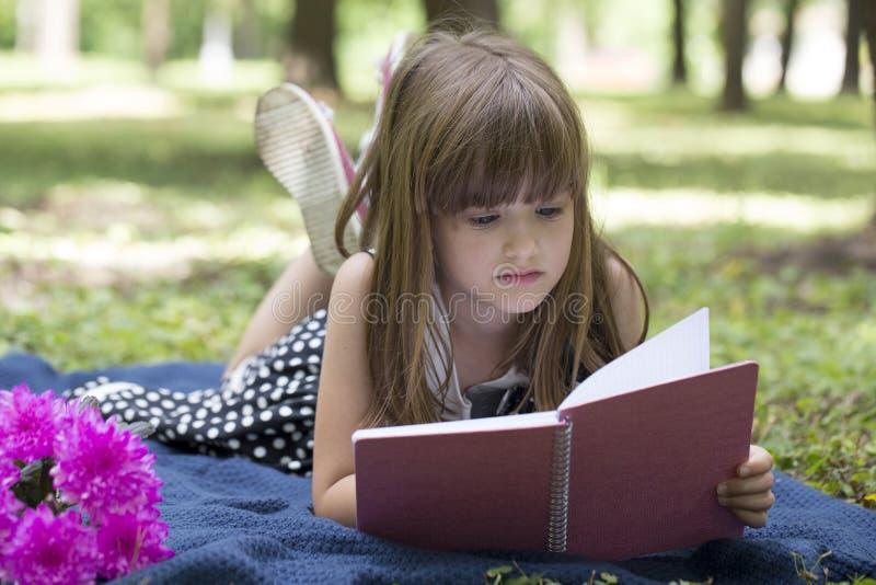 Bambina sveglia con le bugie sull'erba e sulla lettura del libro fotografia stock