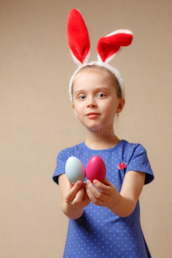 Bambina sveglia con le orecchie del coniglietto e le uova di Pasqua Fuoco selettivo immagini stock libere da diritti