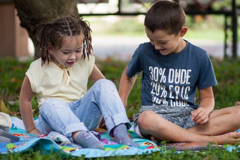 Bambina sveglia con le trecce in una maglietta gialla ed in un ragazzo dentro fotografia stock