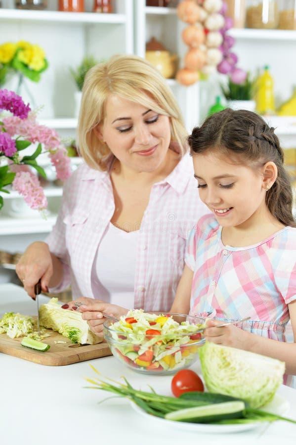 Bambina sveglia con sua madre che cucina insieme al tavolo da cucina fotografia stock libera da diritti
