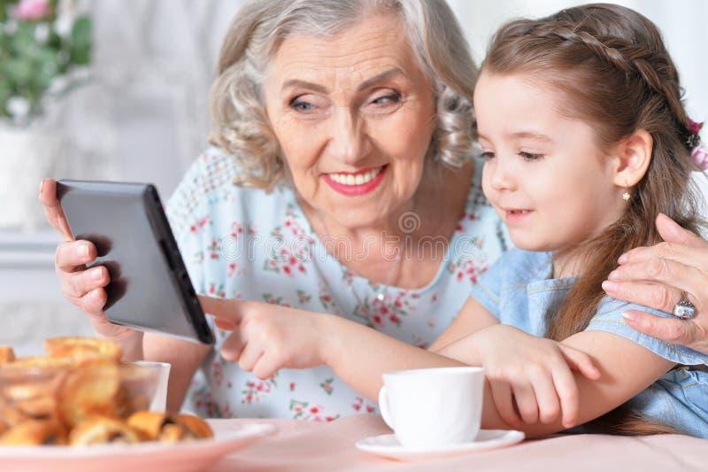 Bambina sveglia con sua nonna che esamina compressa fotografia stock libera da diritti