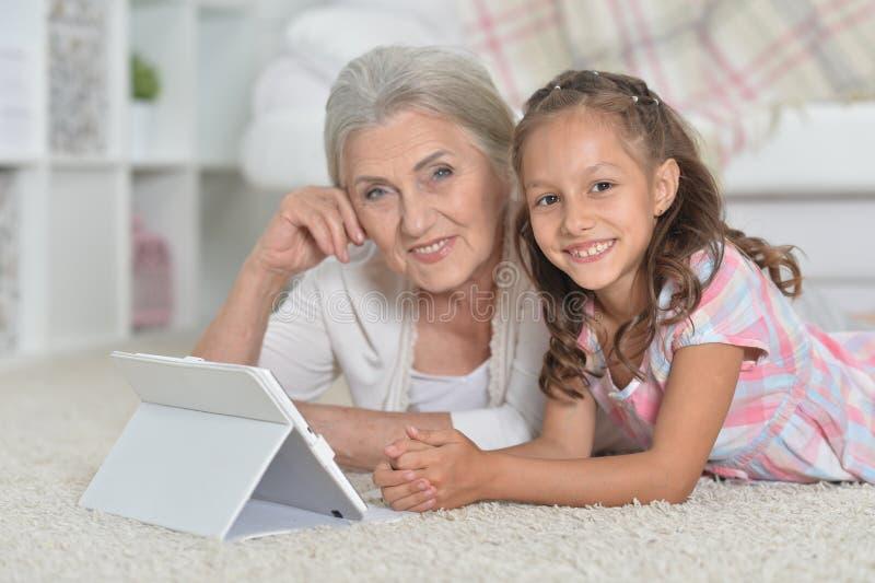 Bambina sveglia con sua nonna che esamina tatble immagine stock