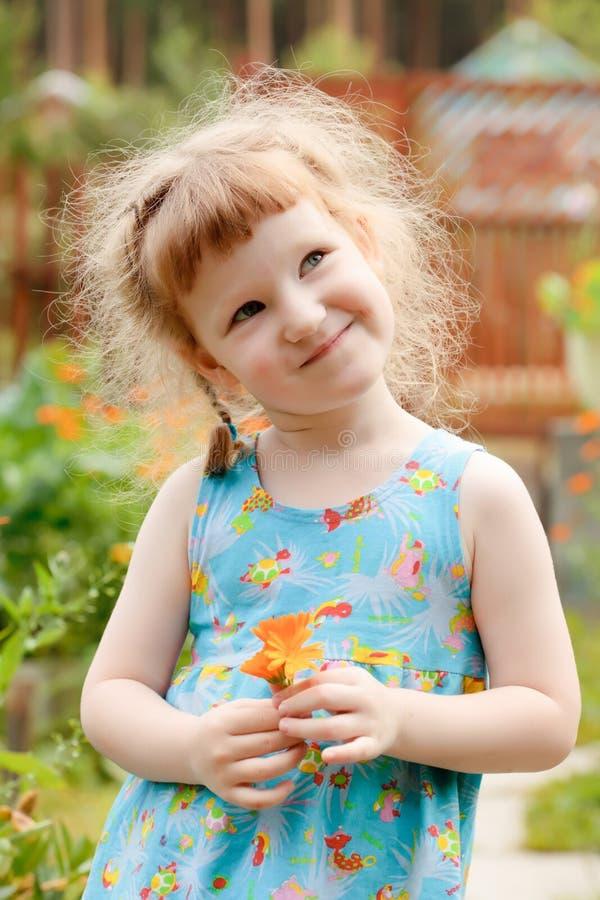 Bambina sveglia con un fiore fotografia stock libera da diritti