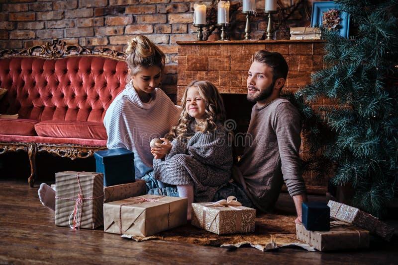 Bambina sveglia di felicità che si siede con i suoi genitori su un pavimento circondato dai regali, accanto al camino ed al natal fotografia stock