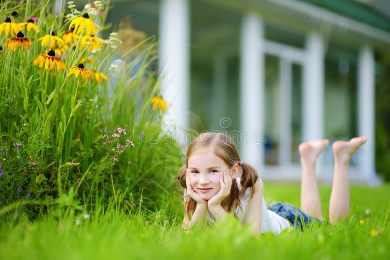 Bambina sveglia divertendosi su un'erba nel suo cortile posteriore immagini stock