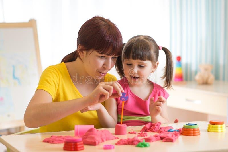 Bambina sveglia e madre che giocano con la sabbia cinetica a casa fotografia stock