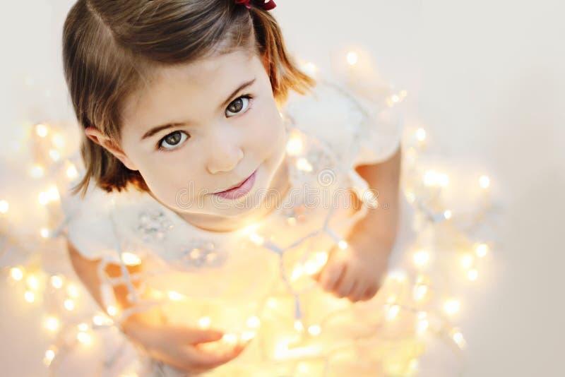 Bambina sveglia e sorridente con le luci di Natale d'ardore fotografia stock