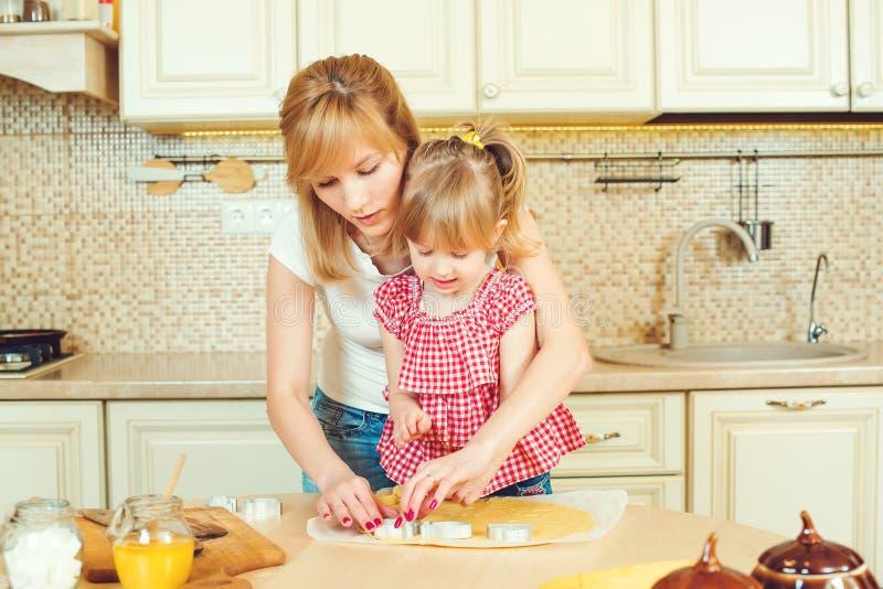 Bambina sveglia e sua la madre che preparano i biscotti facendo uso delle taglierine del biscotto, potate in una cucina fotografie stock