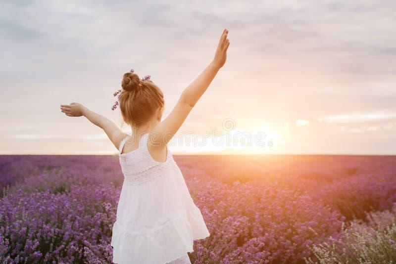 Bambina sveglia felice nel giacimento della lavanda al tramonto Concetto di libertà immagine stock