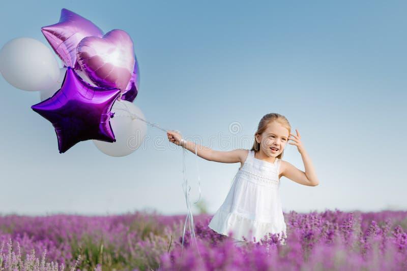 Bambina sveglia felice nel giacimento della lavanda con i palloni porpora Concetto di libertà fotografia stock libera da diritti
