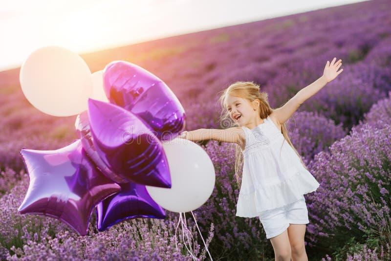 Bambina sveglia felice nel giacimento della lavanda con i palloni porpora Concetto di libertà fotografie stock libere da diritti