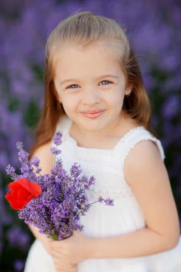 Bambina sveglia felice nel mazzo della tenuta del giacimento della lavanda dei fiori porpora immagini stock libere da diritti