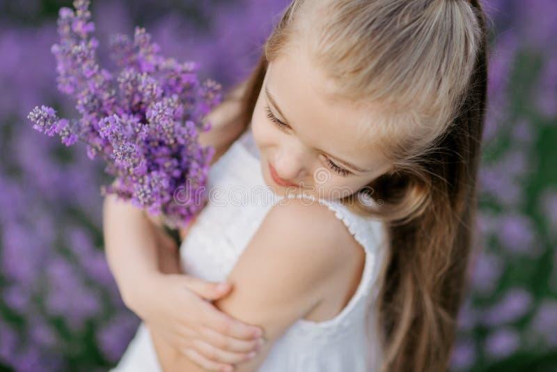 Bambina sveglia felice nel mazzo della tenuta del giacimento della lavanda dei fiori porpora immagine stock