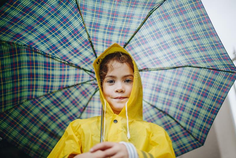 Bambina sveglia in impermeabile con l'ombrello immagine stock