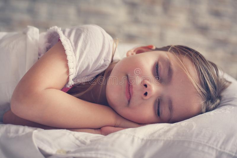 Bambina sveglia a letto immagini stock