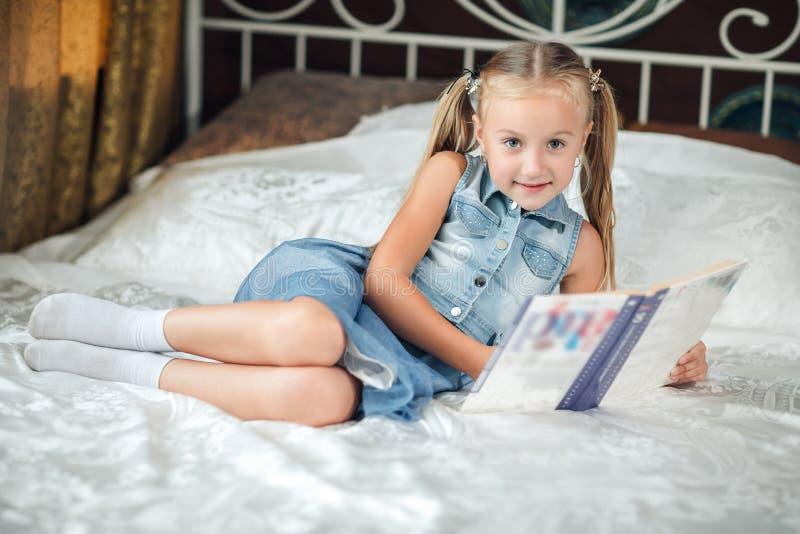 Bambina sveglia in libro di lettura di prendisole del denim che esamina macchina fotografica e che sorride sul letto a casa immagini stock