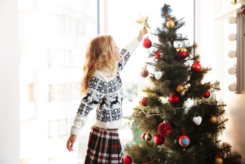 Bambina sveglia in maglione tricottato che dispone stella sulla cima della C immagine stock