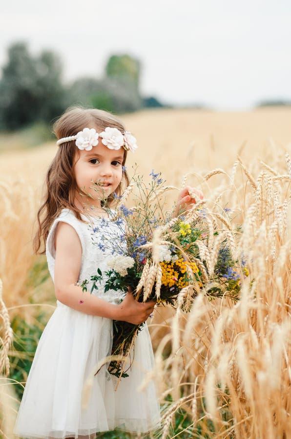 Bambina sveglia nel campo di estate di grano Un bambino con un mazzo dei wildflowers in sue mani fotografia stock