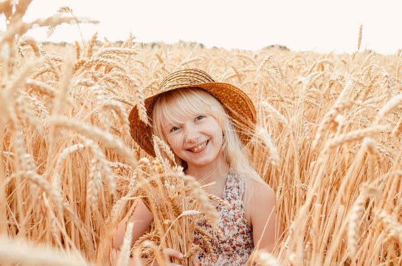 Bambina sveglia nel campo di estate di grano Un bambino con un mazzo di grano in sue mani fotografia stock