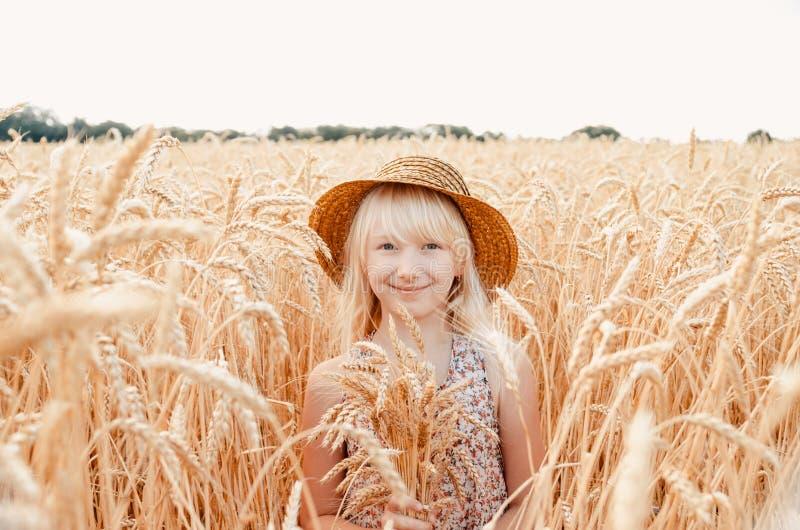 Bambina sveglia nel campo di estate di grano Un bambino con un mazzo di grano in sue mani fotografia stock libera da diritti