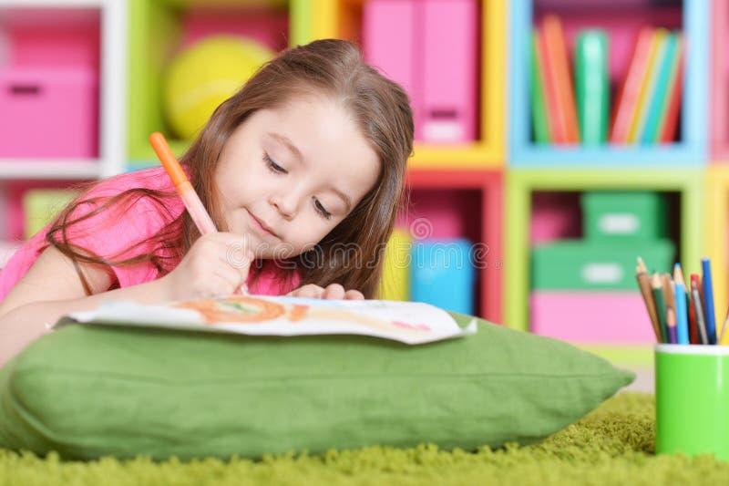 Bambina sveglia nel disegno rosa della camicia mentre trovandosi sul pavimento immagini stock libere da diritti