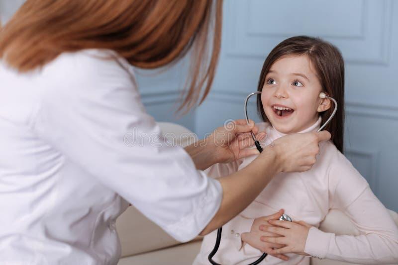 Bambina sveglia positiva che gioca con lo stetoscopio fotografia stock