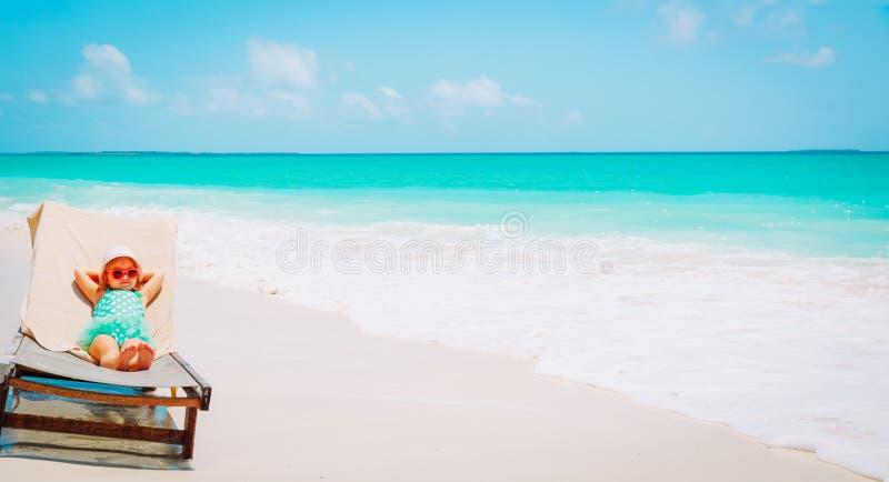 Bambina sveglia rilassata sulla spiaggia di estate fotografia stock libera da diritti