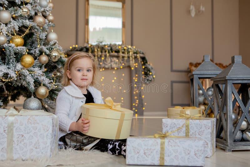 Bambina sveglia sorridente che apre un regalo di Natale, l'albero di Natale del fondo fotografie stock