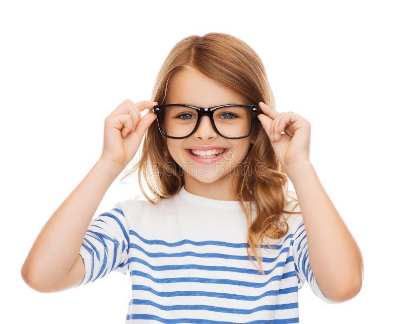Bambina sveglia sorridente con gli occhiali neri fotografia stock