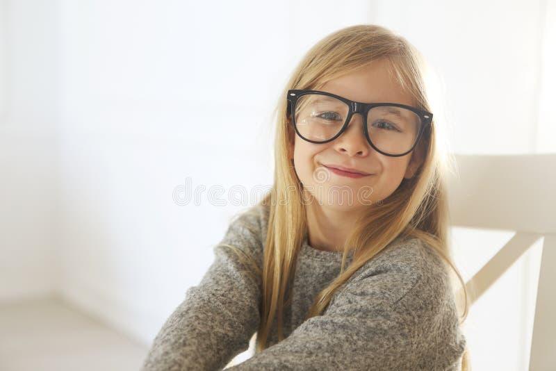 Bambina sveglia sorridente con gli occhiali neri sopra fondo bianco immagini stock