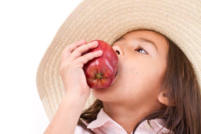 Bambina sveglia, tenuta della mano, mela rossa mordace immagine stock libera da diritti