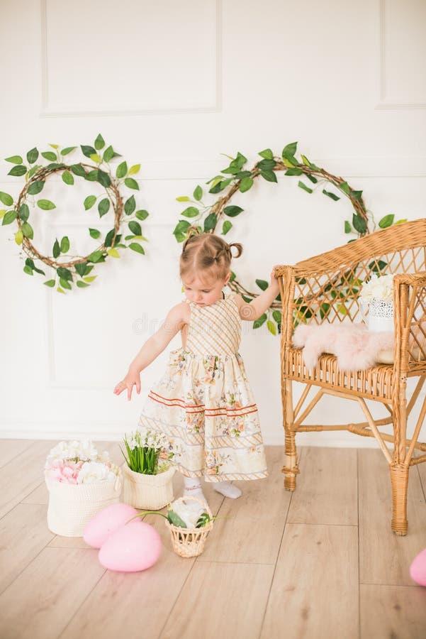 Bambina sveglia in un vestito con una stampa floreale nelle decorazioni di Pasqua nello studio Bambina con le uova di Pasqua ed i immagini stock