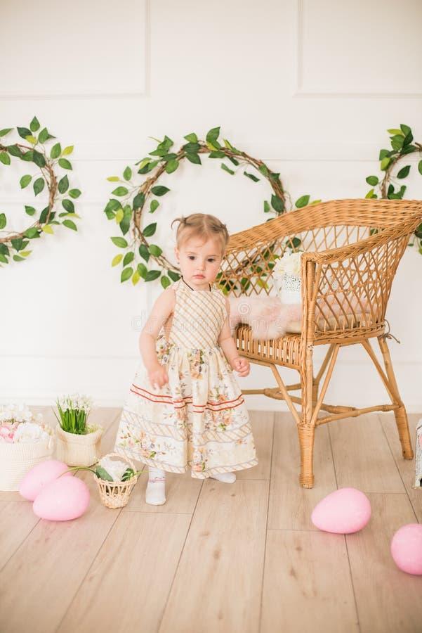 Bambina sveglia in un vestito con una stampa floreale nelle decorazioni di Pasqua nello studio Bambina con le uova di Pasqua ed i immagine stock