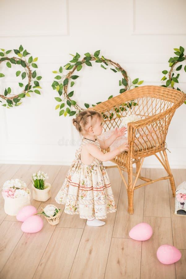 Bambina sveglia in un vestito con una stampa floreale nelle decorazioni di Pasqua nello studio Bambina con le uova di Pasqua ed i immagine stock libera da diritti