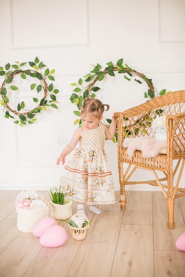 Bambina sveglia in un vestito con una stampa floreale nelle decorazioni di Pasqua nello studio Bambina con le uova di Pasqua ed i fotografia stock libera da diritti